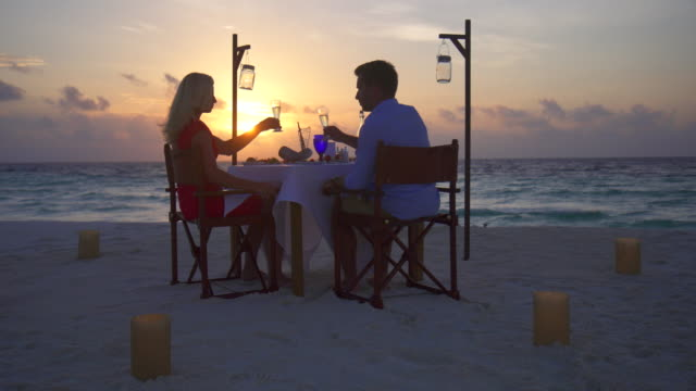 A man and woman couple dine and drink champagne on a tropical island beach.
