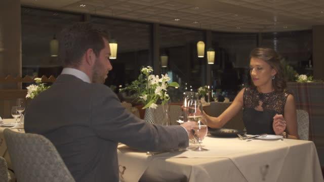 vídeos de stock, filmes e b-roll de a man and woman couple dining in a luxury restaurant. - decoração