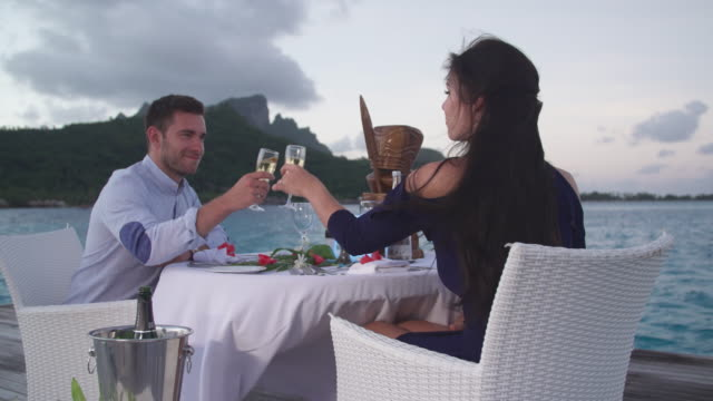 vídeos de stock, filmes e b-roll de a man and woman couple dining on a deck pier at night in bora bora tropical island. - estação turística