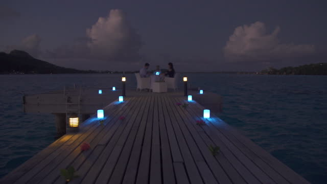 vídeos de stock, filmes e b-roll de a man and woman couple dining on a deck pier at night in bora bora tropical island. - polinésia francesa