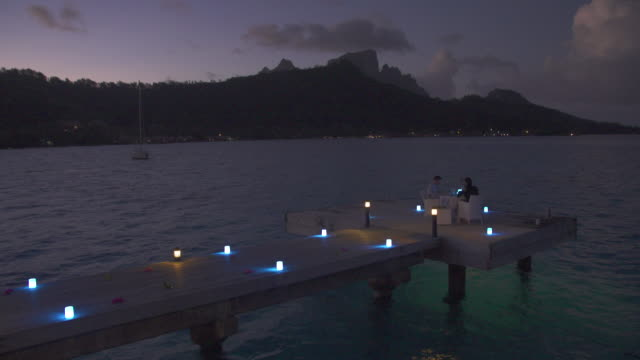 A man and woman couple dining on a deck pier at night in Bora Bora tropical island.