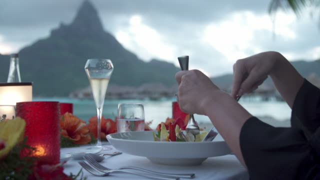 vidéos et rushes de a man and woman couple dining outside at dinner at a tropical island resort. - romantisme