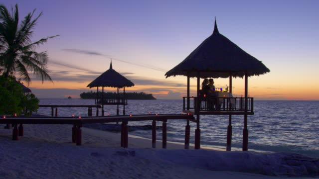 A man and woman couple eat dinner and dine in a hut on a tropical island beach.