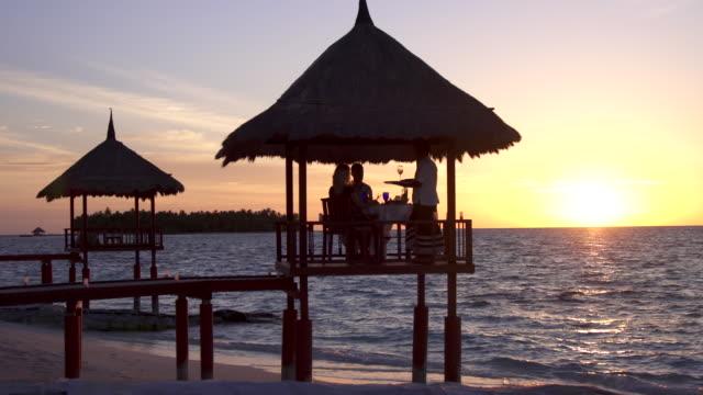 vídeos de stock e filmes b-roll de a man and woman couple eat dinner and dine in a hut on a tropical island beach. - cabana estrutura construída