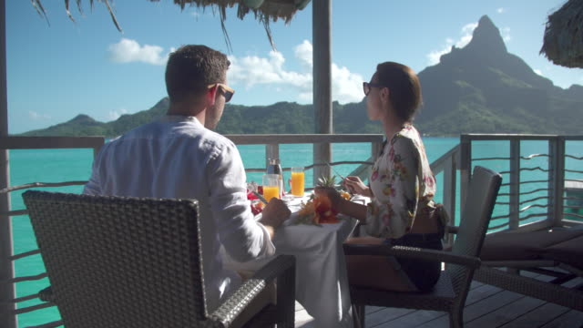 vídeos de stock, filmes e b-roll de a man and woman couple eating breakfast outside at a tropical island resort. - south pacific ocean