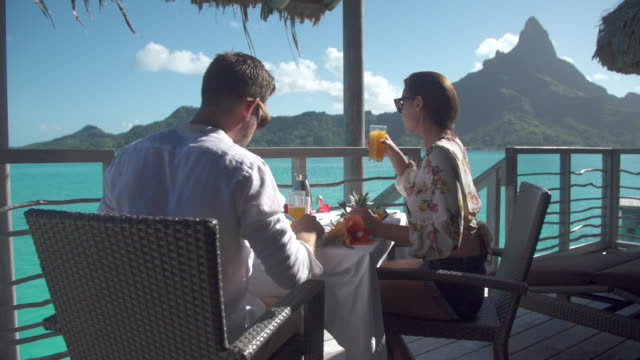 a man and woman couple eating breakfast outside at a tropical island resort. - brunch stock videos and b-roll footage