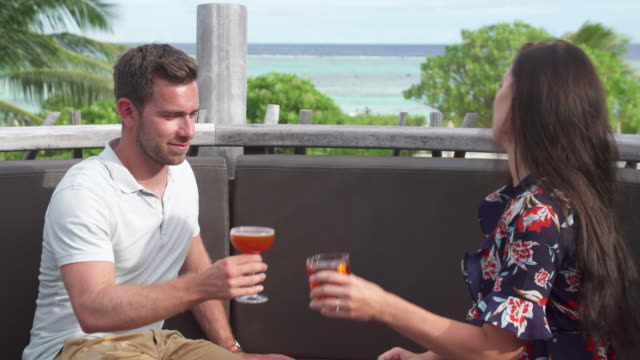 a man and woman couple have a drink on a tropical island. - tropical drink stock videos & royalty-free footage