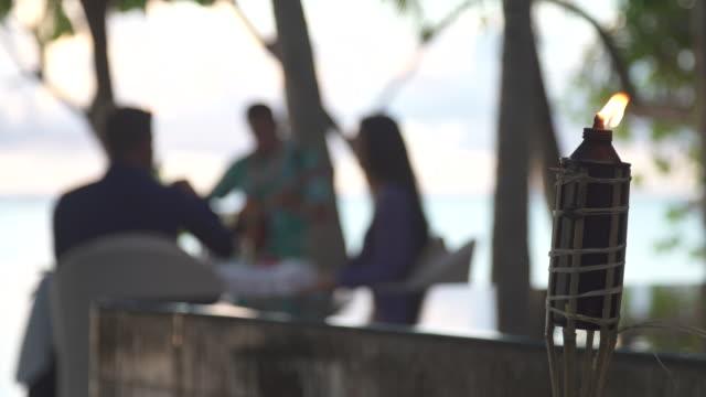 vídeos de stock, filmes e b-roll de a man and woman couple have a drink on a tropical island with tiki torch. - tocha tiki