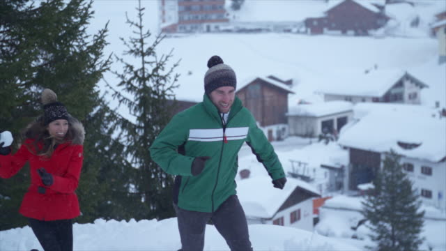 a man and woman couple having a playful snowball fight lifestyle in the snow at a ski resort. - slow motion - skijacke stock-videos und b-roll-filmmaterial