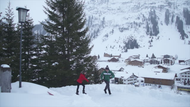 vídeos de stock e filmes b-roll de a man and woman couple having a playful snowball fight lifestyle in the snow at a ski resort. - slow motion - casaco de esqui