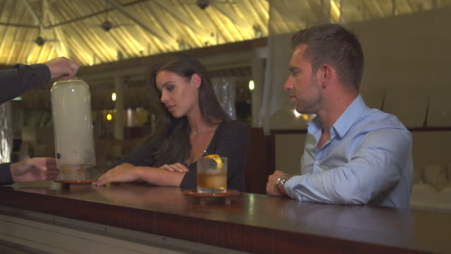 a man and woman couple having a very cold drink at a bar at a tropical island resort. - tropical drink stock videos & royalty-free footage