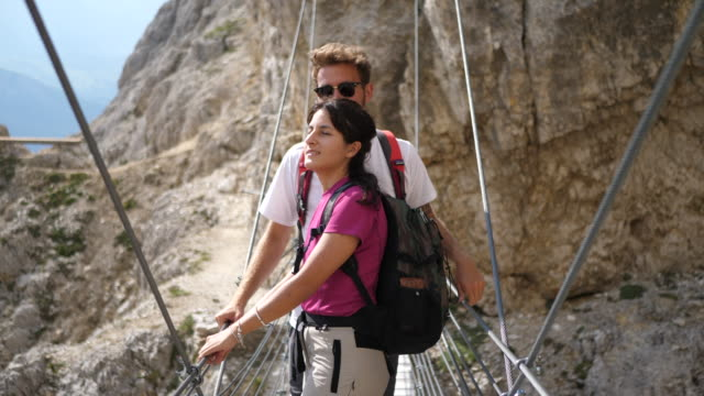 Man and woman couple hiking across a bridge in the mountains.