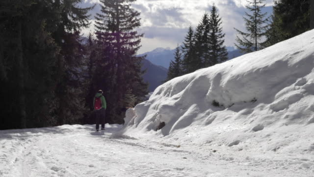 vidéos et rushes de a man and woman couple hiking in the snow in mountains in the winter. - slow motion - couvre chef
