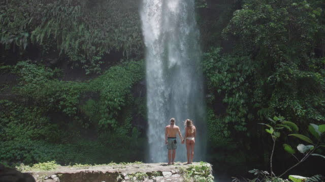 vidéos et rushes de man and woman couple holding hands under a waterfall scenic view in exotic tropical bali, indonesia. - paradisiaque