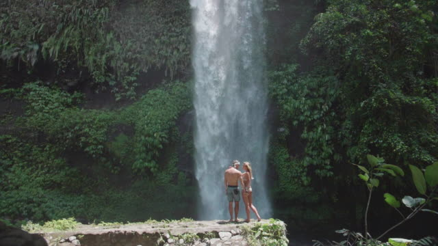 man and woman couple holding hands under a waterfall scenic view in exotic tropical bali, indonesia. - idyllic video stock e b–roll