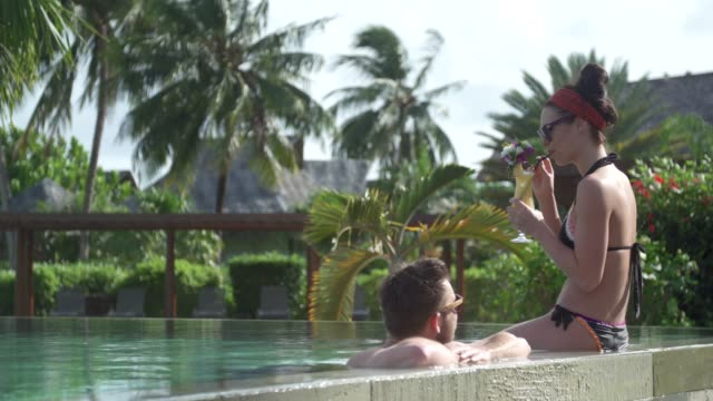 vidéos et rushes de a man and woman couple in a hot tub hot tub spa at a hotel resort. - french overseas territory