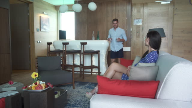 a man and woman couple in a living room of a luxury hotel room at a tropical island resort. - 映像技法点の映像素材/bロール