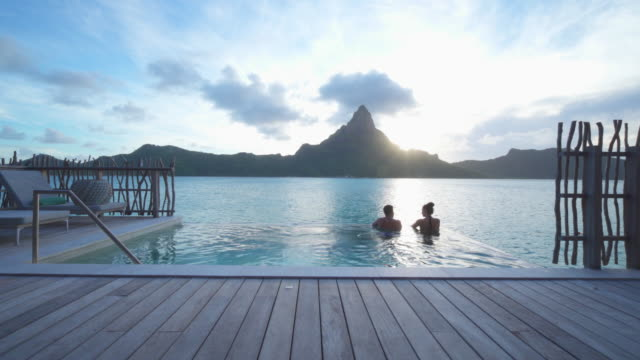 A man and woman couple in a private pool, lifestyle in a pool on Bora Bora with Mount Otemanu at a tropical island resort. - Time-Lapse