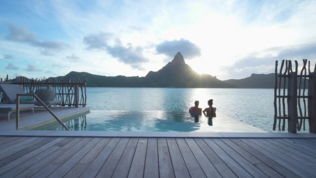 A man and woman couple in a private pool, lifestyle in a pool on Bora Bora with Mount Otemanu at a tropical island resort.