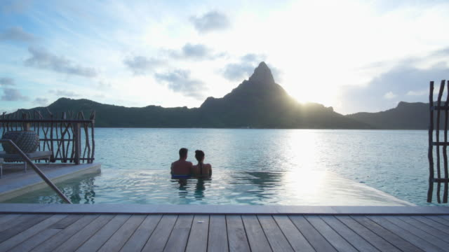 a man and woman couple in a private pool, lifestyle in a pool on bora bora with mount otemanu at a tropical island resort. - idyllic video stock e b–roll
