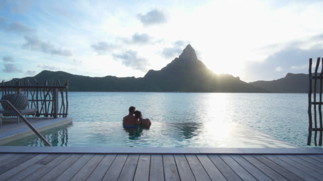a man and woman couple in a private pool, lifestyle in a pool on bora bora with mount otemanu at a tropical island resort. - patio stock-videos und b-roll-filmmaterial