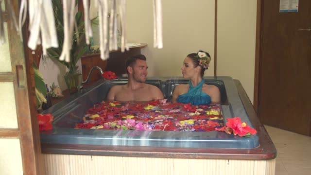 vidéos et rushes de a man and woman couple in an in room hot tub hot tub spa at a hotel resort. - french overseas territory