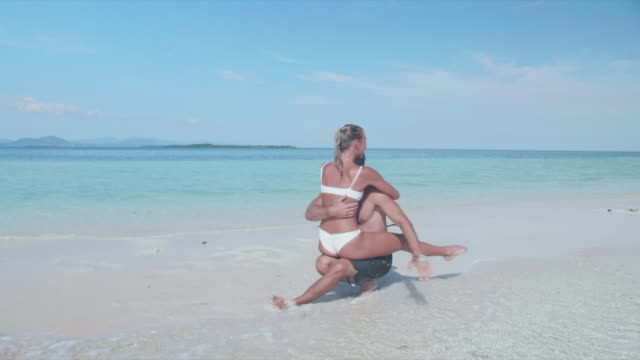 a man and woman couple in swimwear kissing and hugging on a sandbar tropical island in the sea. - zen like stock videos & royalty-free footage