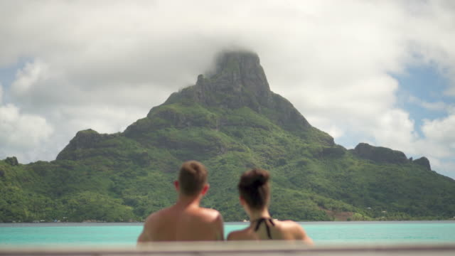 A man and woman couple lifestyle in a pool on Bora Bora with Mount Otemanu at a tropical island resort.