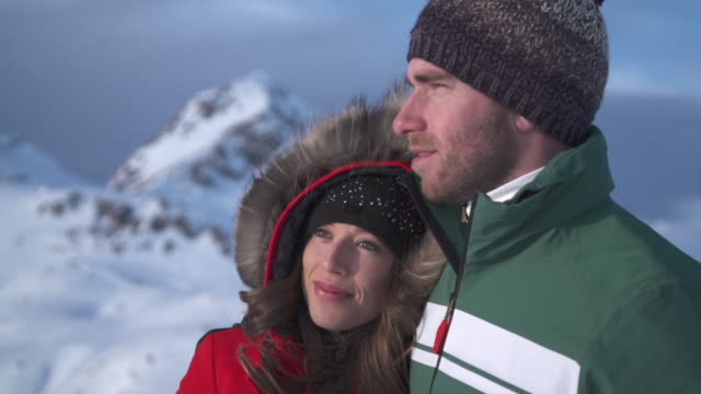a man and woman couple lifestyle in the snow at a ski resort. - skijacke stock-videos und b-roll-filmmaterial