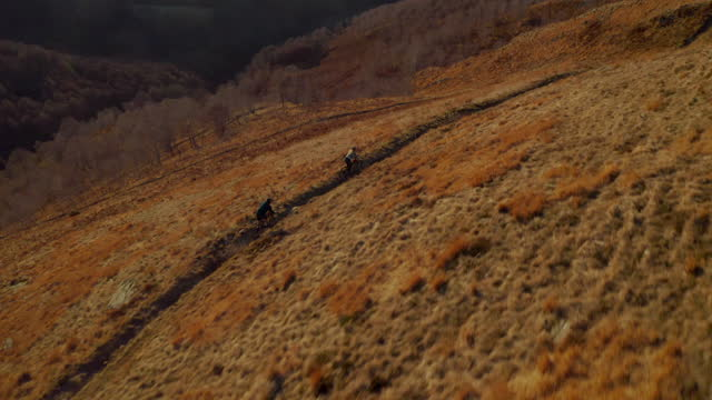 man and woman couple pushing bicycles up a grassy mountain path with lake behind at sunset - サイクリングロード点の映像素材/bロール