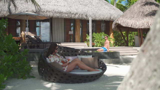 a man and woman couple relaxing and reading a book in the tropical islands in french polynesia. - libro in brossura video stock e b–roll