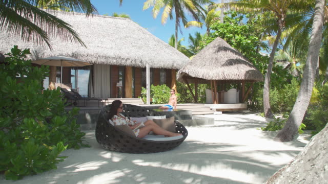 a man and woman couple relaxing and reading a book in the tropical islands in french polynesia. - paperback stock videos & royalty-free footage