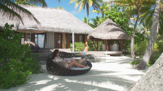 a man and woman couple relaxing and reading a book in the tropical islands in french polynesia. - territori francesi d'oltremare video stock e b–roll