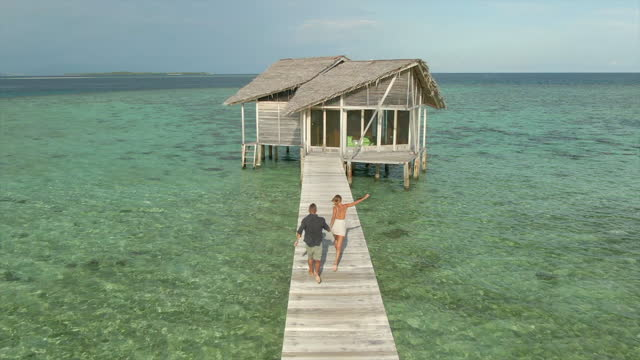 man and woman couple running on deck pier at scenic tropical island in over water bungalow hotel resort, aerial drone view. - slow motion - island stock videos & royalty-free footage