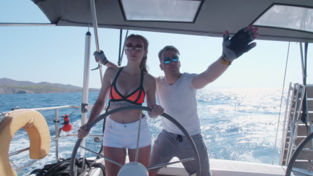 vidéos et rushes de a man and woman couple sailing steering a sailboat in the aegean sea of greece. - sport aquatique