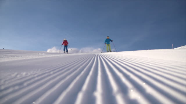 a man and woman couple skiing together in the snow at a ski resort. - slow motion - paar mittleren alters stock-videos und b-roll-filmmaterial
