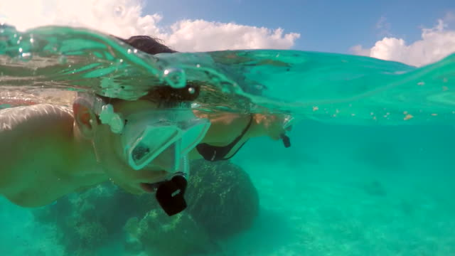 A man and woman couple snorkeling over the coral reef of a tropical island. - Slow Motion
