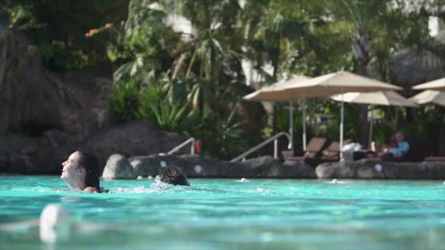 vídeos y material grabado en eventos de stock de a man and woman couple swimming in a pool at a hotel resort in tahiti. - slow motion - riqueza