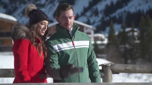 vídeos y material grabado en eventos de stock de a man and woman couple take a selfie photograph lifestyle in the snow at a ski resort. - chaqueta de esquiar
