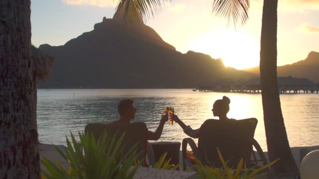 a man and woman couple toasting and drinking drinks at a tropical island resort with the lagoon and mount otemanu. - tourist resort stock videos & royalty-free footage