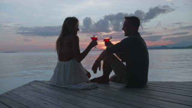 a man and woman couple toasting cheers traveling scenic tropical island in overwater bungalow hotel resort in a lagoon. - hotel stock-videos und b-roll-filmmaterial