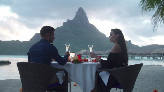 a man and woman couple toasting with champagne on the beach of a tropical island resort at sunset in bora bora. - evening meal stock videos and b-roll footage