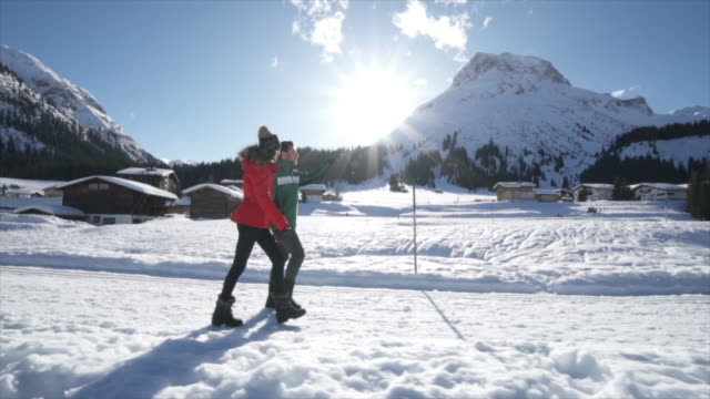 a man and woman couple walking in the snow at a ski resort in the snow at the mountains. - skijacke stock-videos und b-roll-filmmaterial