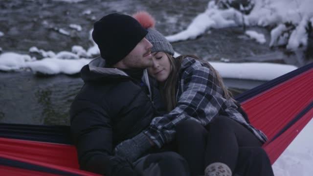 man and woman cuddling in hammock during winter - american fork canyon bildbanksvideor och videomaterial från bakom kulisserna