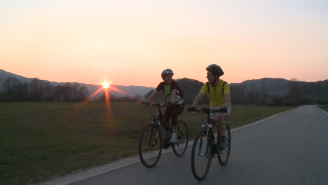 stockvideo's en b-roll-footage met ws ds man and woman cycling in rural landscape at sunset, vrhnika, slovenia - vrhnika