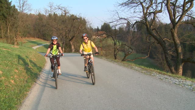 stockvideo's en b-roll-footage met ws ds man and woman cycling in rural landscape, vrhnika, slovenia - vrhnika