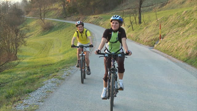 stockvideo's en b-roll-footage met slo mo ws ds man and woman cycling in rural landscape, vrhnika, slovenia - vrhnika