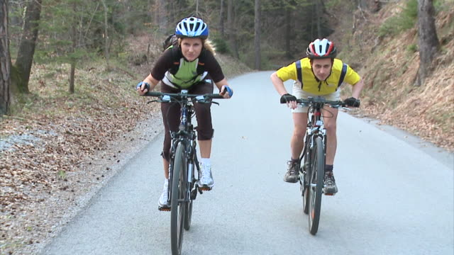 stockvideo's en b-roll-footage met slo mo ms ds man and woman cycling in rural landscape, vrhnika, slovenia - vrhnika