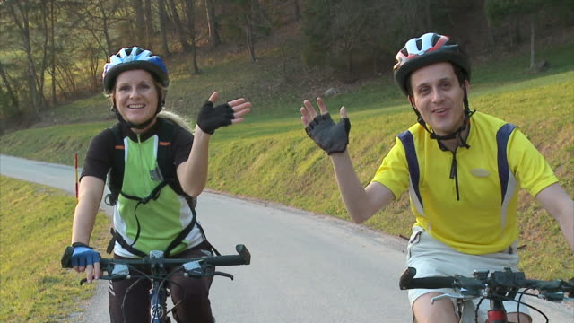slo mo ms ds man and woman cycling in rural landscape, waving to camera, vrhnika, slovenia - vrhnika stock videos & royalty-free footage