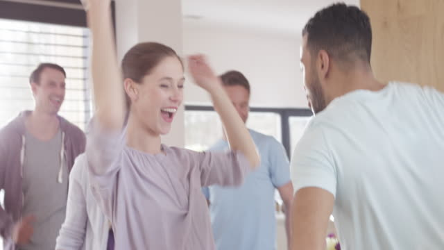Man and woman dancing at a party with friends